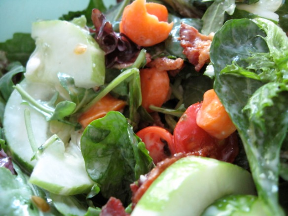 Tomatoes in salad with carrot, cucumber, sunflower shoots.