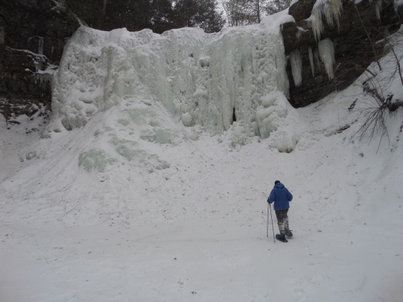 Away, snowshoeing to the base of the frozen sixty foot tall falls at Plotterkill Creek.